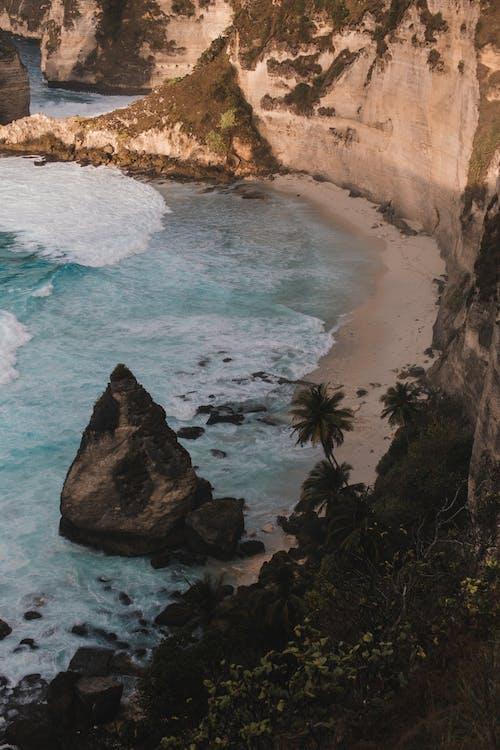 Big boulder in blue sea with steep coast