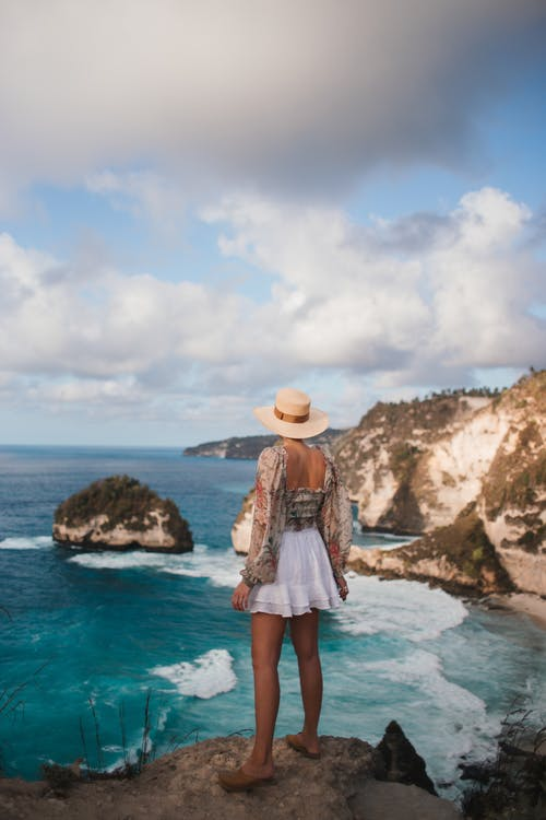 Back view of anonymous traveler in straw hat admiring foamy ocean and mounts under blue cloudy sky