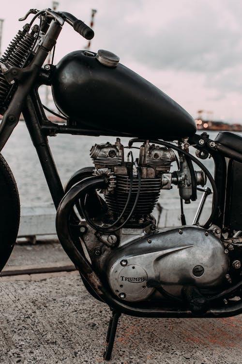 Retro motorcycle engine on embankment against sea