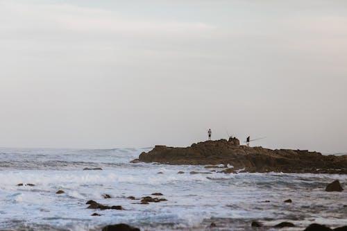 Faceless fishermen on rock catching fish in sea