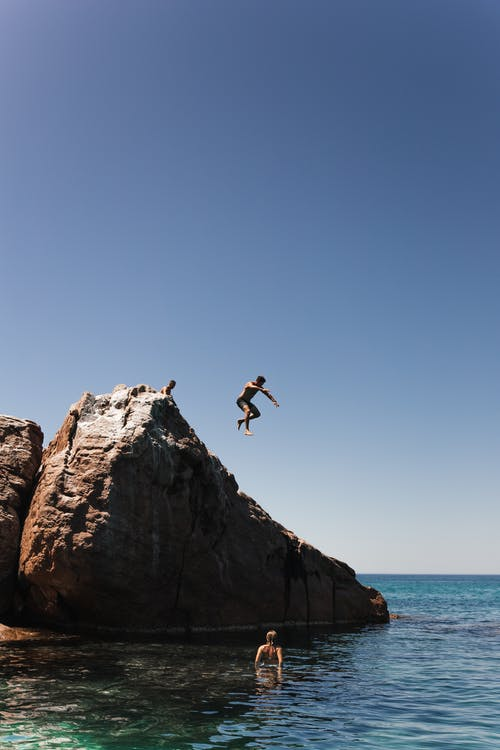 Unrecognizable man jumping off cliff into clear blue water on summer sunny day