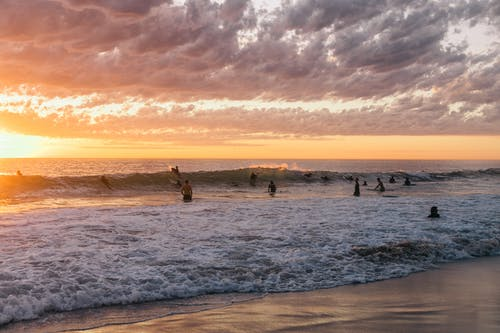 Silhouettes of surfers spending time in ocean with foamy waves splashing towards sandy shore at bright sunset on horizon