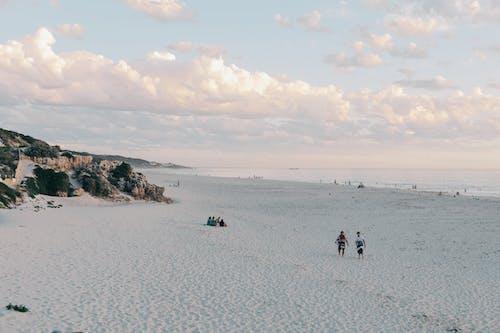 Tourists resting on sandy beach near ocean in evening