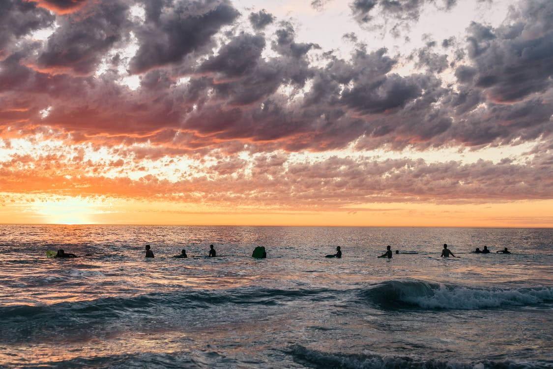 Silhouettes of people with surfboards standing in deep blue ocean water while watching picturesque bright sunset on horizon and cumulus clouds