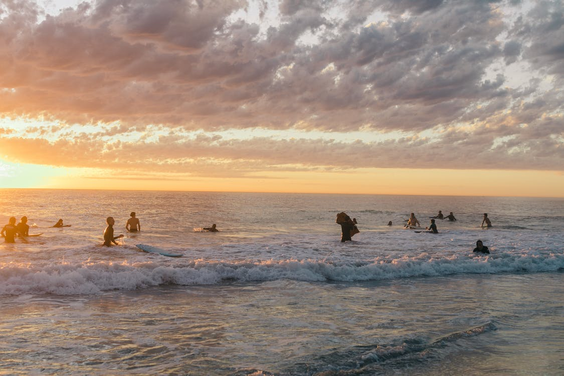 Unrecognizable tourists in swimwear admiring sea waves while swimming and splashing in water in summer evening