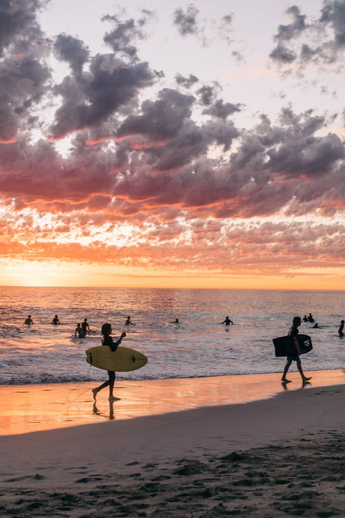 Unrecognizable people in swimsuits enjoying summer sunset on sandy beach near calm ocean while swimming and surfing