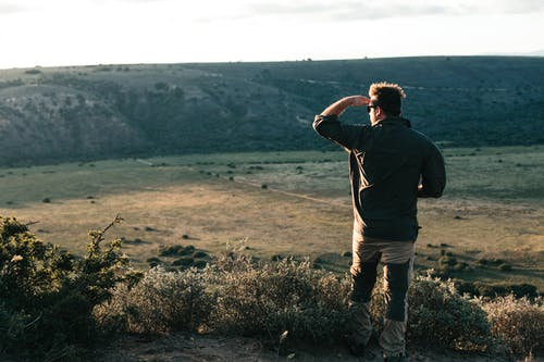 Unrecognizable traveler standing on hilltop in daytime