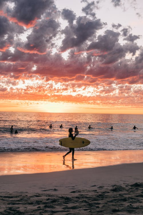 Unrecognizable people in swimwear surfing and swimming on sandy summer beach in calm sea at sundown