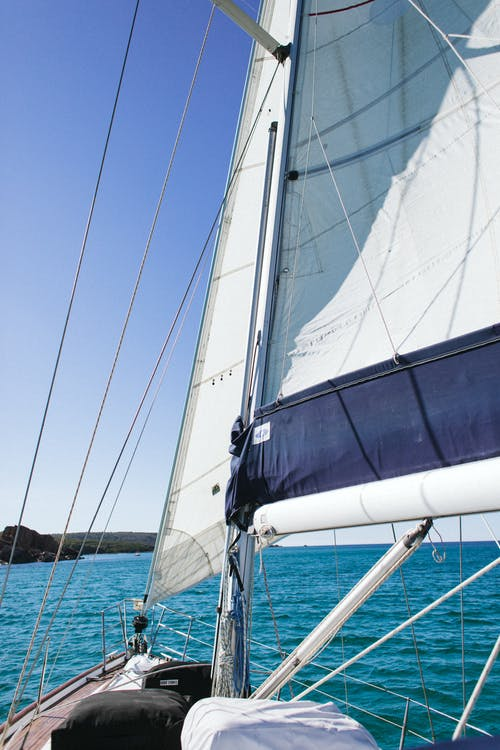 Yacht with white sail floating on blue rippling sea water to green coast
