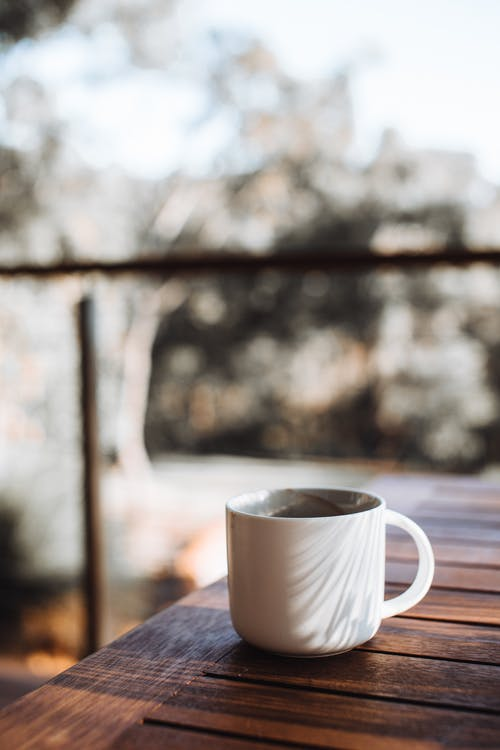 White ceramic cup of hot drink placed on brown wooden table on terrace