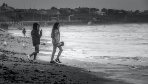 Anonymous adolescents walking on sea beach in storm