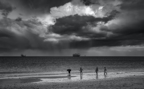 Black and white back view of unrecognizable travelers walking on sandy ocean coast under cloudy sky