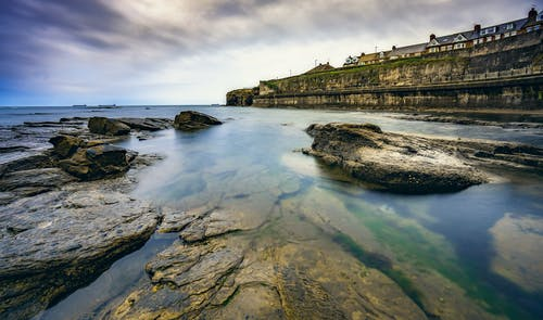 Scenery view of ocean with pure water near rough rocky formations under cloudy sky with horizon near dock with houses