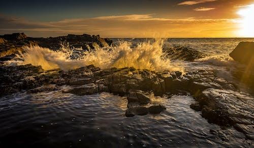Splashing sea water near stones at colorful sunset