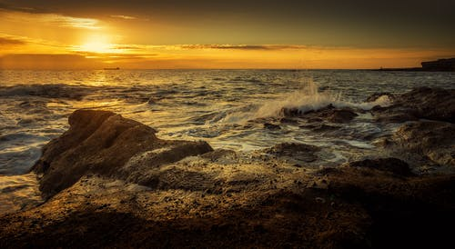Spectacular view of splashing ocean water near stones behind horizon under colorful sky at sunset