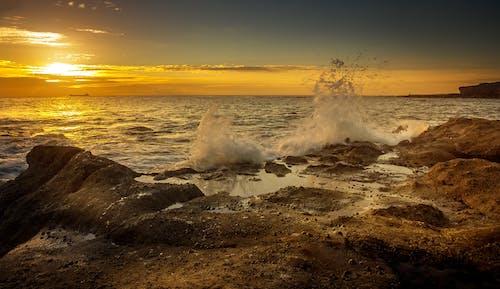 Splashing sea water under bright sky at sundown