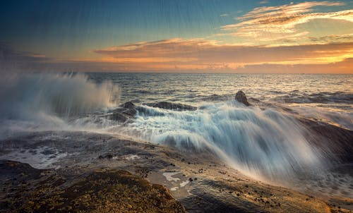 Rapid ocean flow with splatter on stones under bright cloudy sky at sunset in storm