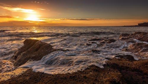 Foamy sea near cliffs under colorful sky at sundown
