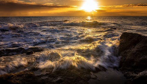 Fast sea water stream with waves and foam under colorful sky with luminous sun in twilight