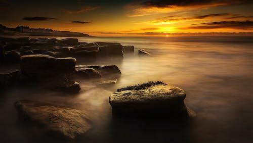Cliffs near foggy ocean under bright sky at sunset
