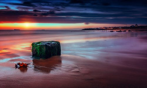 Picturesque view of rocky formation near wavy sea and sandy shore in mist under colorful cloudy sky at sunset