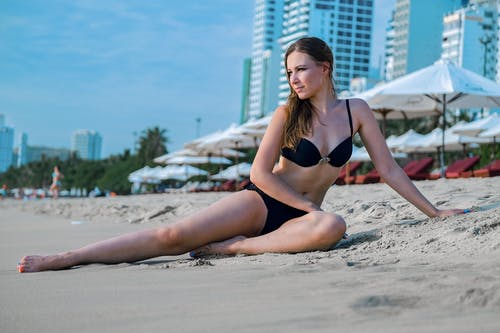 Relaxed young woman sunbathing on sandy seashore