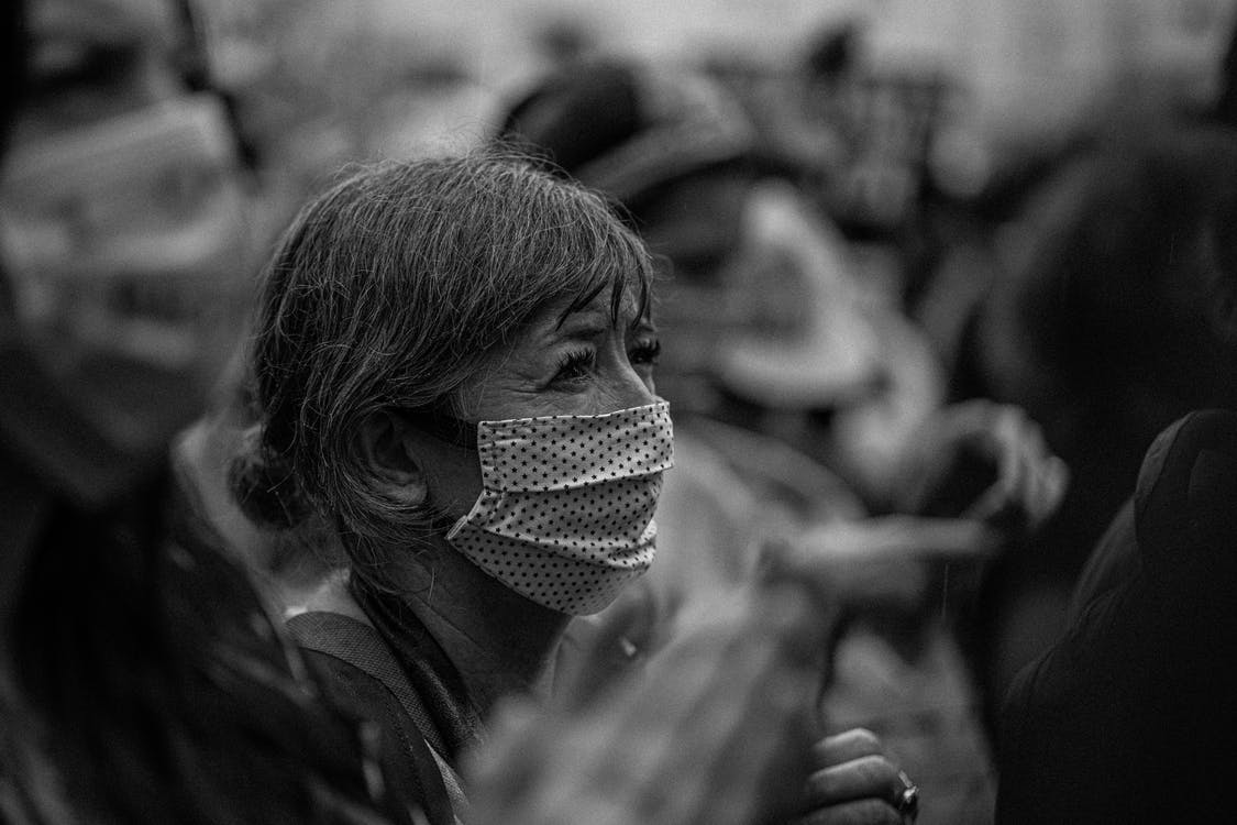 Black and white side view of unrecognizable elderly female in mask during manifestation on city street