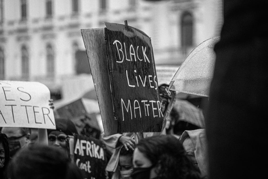 Black and white of anonymous demonstrators with cardboard placards during activist movement fighting for social justice and equality on street