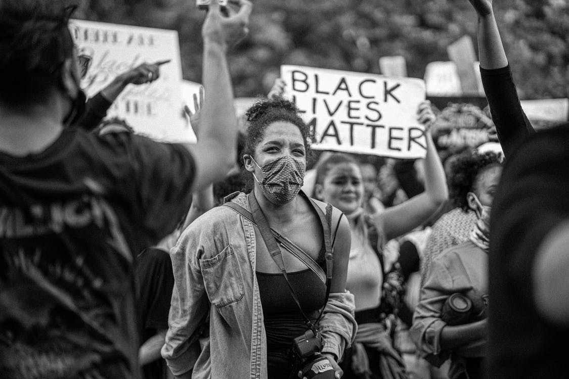 Black and white of demonstrators showing cardboard placards with Black Lives Matter title during strike in town