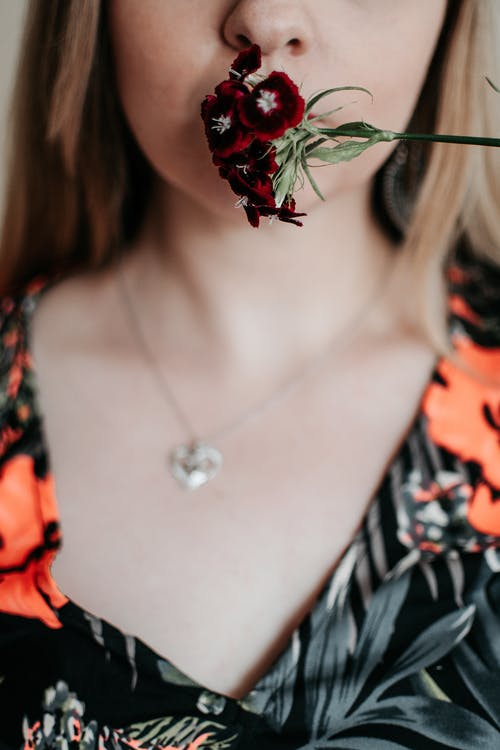 Crop anonymous female in pendant and ornamental wear covering lips with blossoming flower on thin stalk