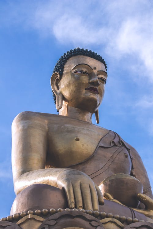 From below of huge bronze Buddha Dordenma statue situated in Bhutan against blue sky