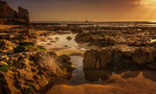 Rough stones near ocean under shiny sky at sundown