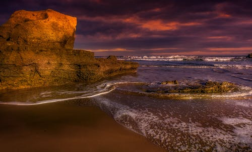 Wavy ocean near rough cliff and sandy shore under bright cloudy sky at sundown in stormy weather