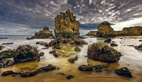 Rocks and rippled sea under cloudy sky