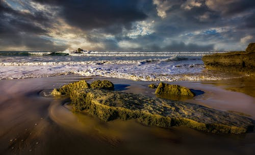 Mossy rocky formations in sea with foamy waves under cloudy sky at sundown