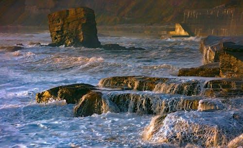 Stormy ocean with foam near cliffs in evening