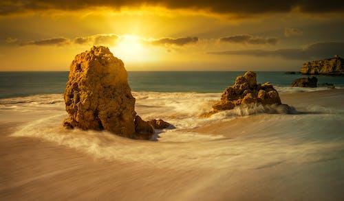 Foamy ocean near cliffs under bright sky at sundown
