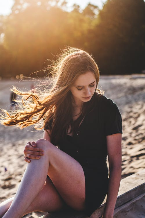 Selective Focus Photography of Woman Sitting Near Sand