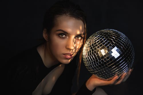 Stylish woman with disco ball in darkness