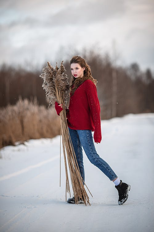 Trendy model with dry grass bouquet on snowy road