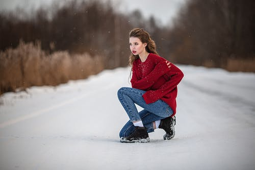 Trendy woman in bright casual clothes on snowy roadway
