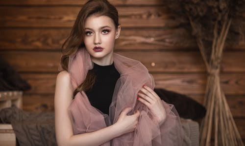 Stylish woman with makeup near wooden wall