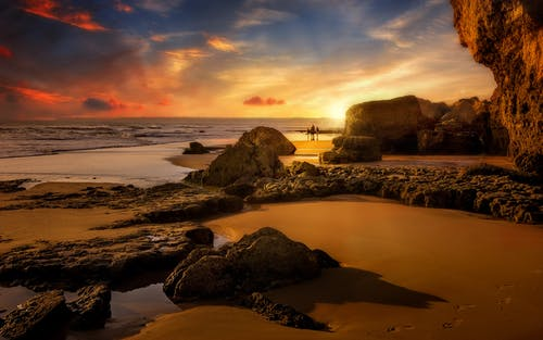 Rocky formations near wavy sea under bright sky at sunset