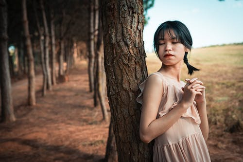 Dreamy tender Asian female in light dress closing eyes and leaning on tree trunk in sunny day