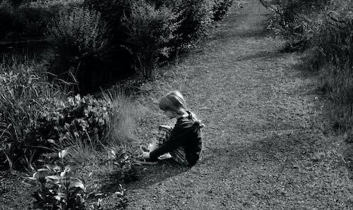 Foto profissional grátis de menino sapato trilha sentado jardim