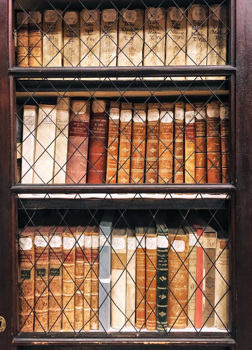 Stack of various books arranged in rows on old fashioned wooden shelf with ornamental glass