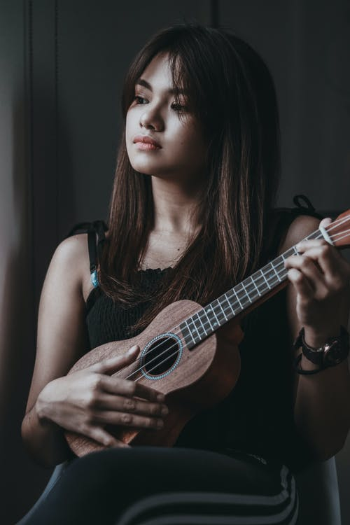 Dreamy young ethnic female musician in casual clothes playing ukulele and looking away pensively