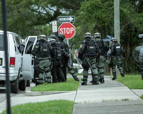 2 Men in Black and Gray Camouflage Uniform Standing on Sidewalk