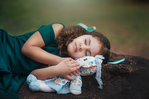 Adorable ethnic little girl with curly hair in dress hugging soft toy while sleeping on ground in park