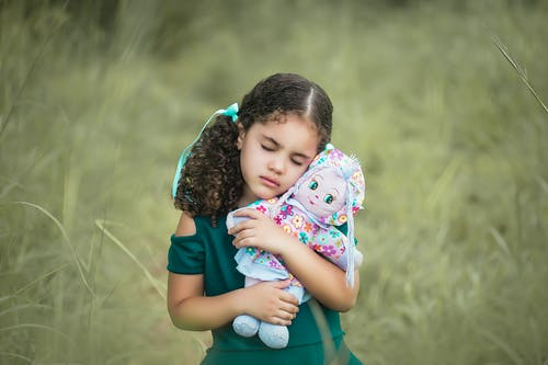 Peaceful little girl with curly pigtails in dress embracing soft doll with closed eyes while resting in meadow in countryside